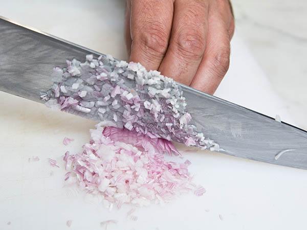 Couteau de cuisine qui coupe une échalote